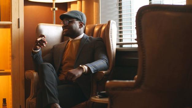 Stijlvol lachende afro-amerikaanse man in een elegante jas en bril, zittend in een stoel in een chique restaurant. rijke, modieuze afro-man