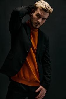 Stijlvol manmodel in een trui en jas houdt zijn hand achter zijn hoofd op een donkere achtergrondkopie