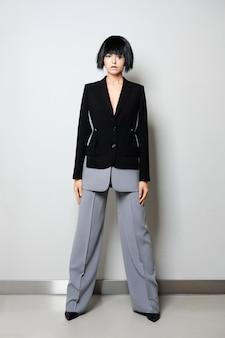 Stijlvol mannequin in korte zwarte pruik poseren in tweekleurig broekpak met wijde broek en jas met diepe snit