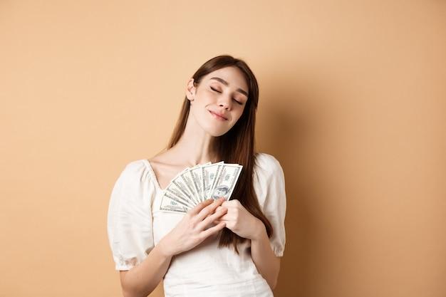 Stijlvol meisje dat geld knuffelt met een tevreden glimlach en gesloten ogen zoals dollarbiljetten die op beige ba...