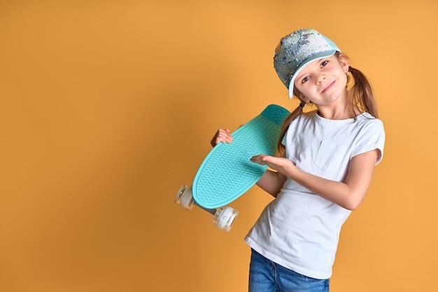 Stijlvol meisje draagt witte t-shirt, blauwe spijkerbroek en groene pet, met skateboard op gele achtergrond