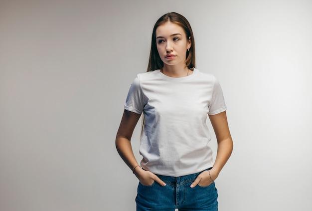 Stijlvol meisje dragen witte t-shirt poseren in studio