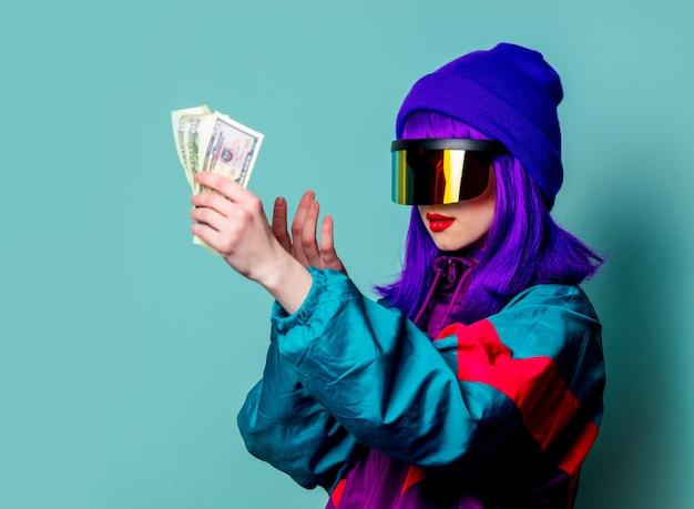 Stijlvol meisje in cyberpunkglazen en trainingspak houdt geld vast op blauwe muur