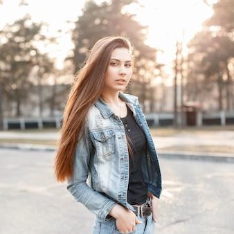 Stijlvol meisje in denimkleren bij zonsondergang