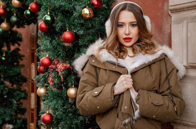 Stijlvol meisje in een jas met bont in de buurt van de kerstboom op straat. jonge vrouw met warme hoofdtelefoons en stromend haar. oorwarmers of winterkoptelefoons. winter.