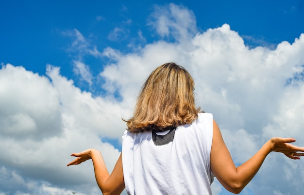Stijlvol meisje in een wit t-shirt staat met haar rug naar de camera tegen een blauwe lucht en spreidt haar armen opzij