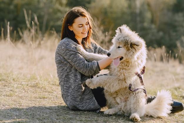Stijlvol meisje in een zonnig veld met een hond