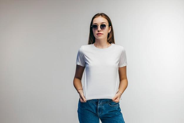 Stijlvol meisje in glazen dragen witte t-shirt poseren in studio