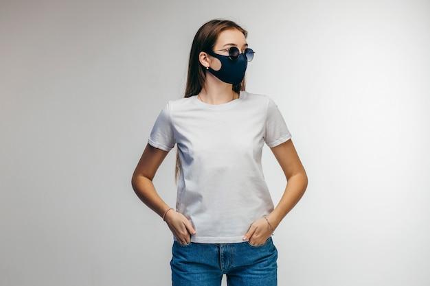 Stijlvol meisje in glazen en beschermend masker dragen witte t-shirt poseren in studio