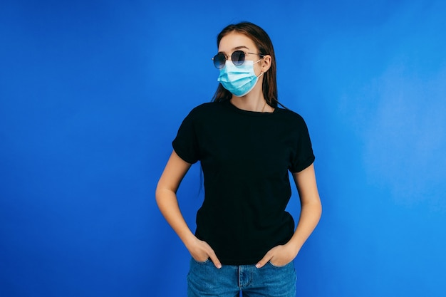 Stijlvol meisje in glazen en beschermend masker dragen zwarte t-shirt poseren in studio op blauwe ruimte