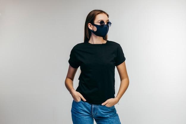 Stijlvol meisje in glazen en beschermend masker dragen zwarte t-shirt poseren in studio