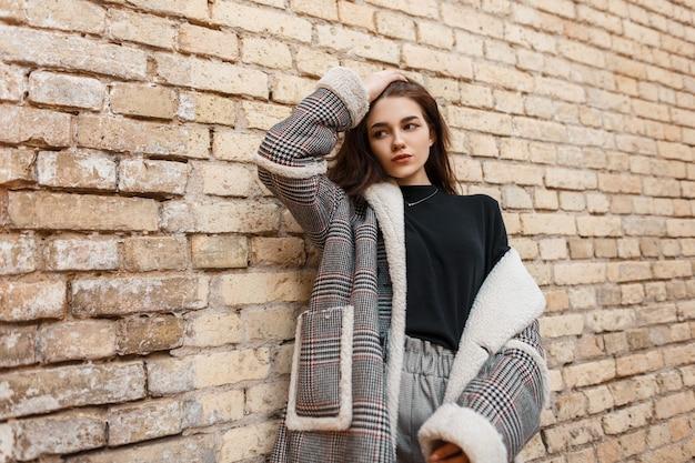 Stijlvol meisje in mode-uitloper vormt op straat