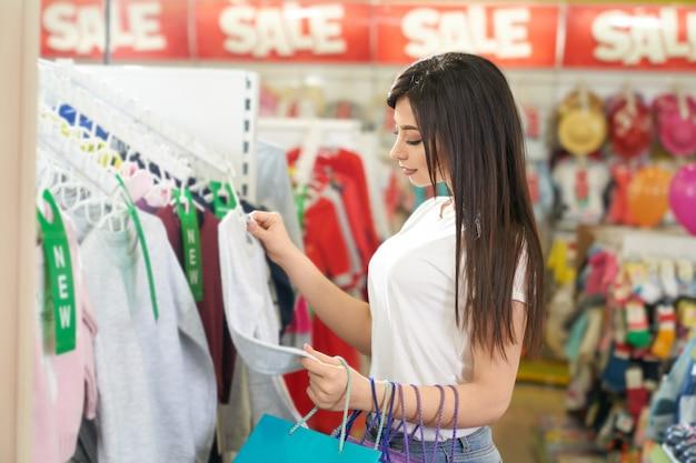 Stijlvol meisje kiezen blouse in kledingwinkel.