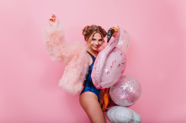 Stijlvol meisje lachen in pluizig roze jasje dansen met ballonnen voor evenementen, vrienden te wachten. schattige jonge vrouw in blauwe bodysuit met plezier met speelgoed flamingo, klaar voor pool party.