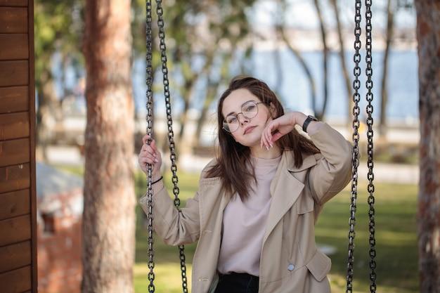 Stijlvol meisje met een bril, buitenshuis. tienermeisje op een schommeling, mooi portret.