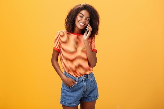 Stijlvol meisje met een donkere huidskleur die een informeel telefoontje pleegt naar een vriend die alle details vertelt van een romantische date die blij en zorgeloos over een oranje achtergrond staat in een gestreept t-shirt en naar links kijkt met een grijns