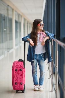 Stijlvol meisje met een koffer op de luchthaven