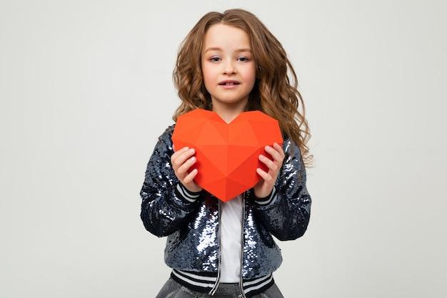 Stijlvol meisje met een papieren hart op een witte muur met lege ruimte