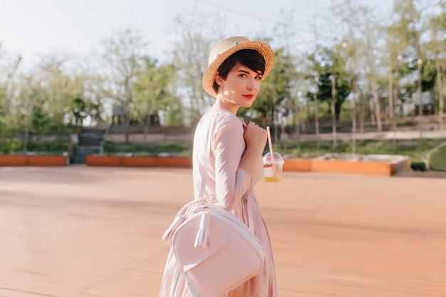 Stijlvol meisje met kort kapsel kijkt met belangstelling over haar schouder tijdens wandeling in park