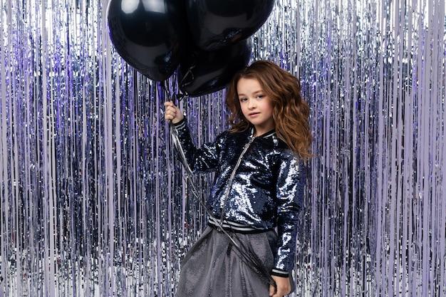 Stijlvol meisje met luchtige zwarte helium ballonnen op een muur van glanzend klatergoud