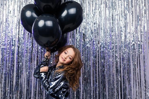 Stijlvol meisje met zwarte ballonnen op een muur van glanzend klatergoud.