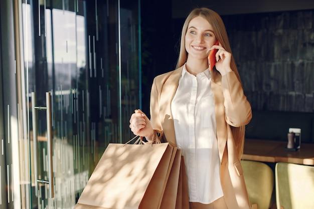 Stijlvol meisje permanent in een café met boodschappentassen