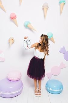 Stijlvol meisje zenuwachtig omdat de gasten te laat zijn voor haar verjaardagsfeestje. aantrekkelijke elegante jonge vrouw die in violette rok grote klok met verbaasde gezichtsuitdrukking bekijkt die zich in ingerichte kamer bevindt.