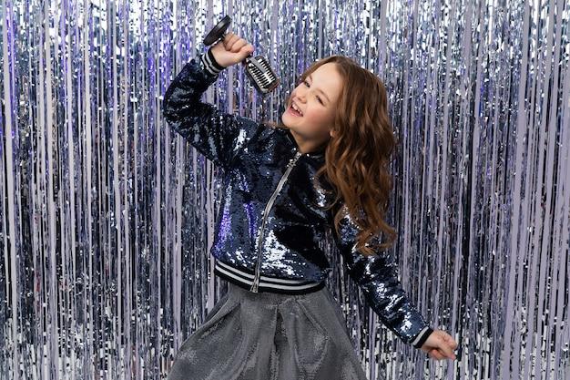 Stijlvol meisje zingt met een microfoon in haar handen en een opgestoken hand