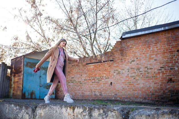 Stijlvol meisjesmodel in een bruine jas, roze pak en grijze laarzen op de stadsruïnes. de trends van de moderne mode. modieus beeld