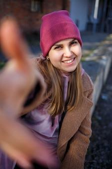 Stijlvol meisjesmodel in een bruine jas, roze pak en roze hoed lacht prachtig. de trends van de moderne mode. modieus beeld. heldere emoties