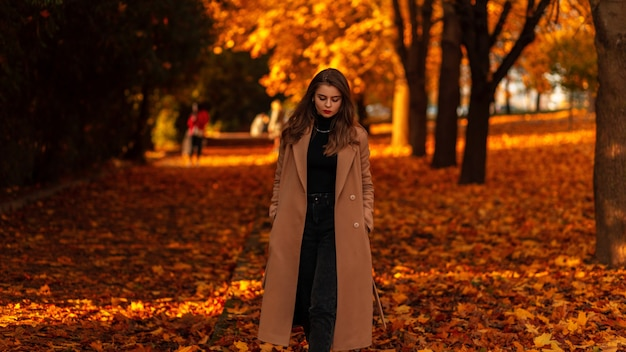 Stijlvol meisjesmodel in een trendy vintage beige jas met een zwarte trui en jeans loopt in een sojapark met geel gebladerte bij zonsondergang