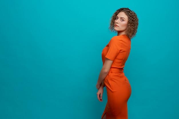 Stijlvol model in oranje jurk staand, poseren.