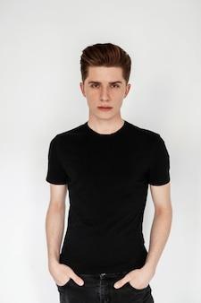 Stijlvol model jonge knappe man met mode kapsel in trendy jeugd casual zwart leeg t-shirt uit nieuwe zomercollectie staat in de buurt van witte muur in studio. verse portret knappe jongen in de kamer.