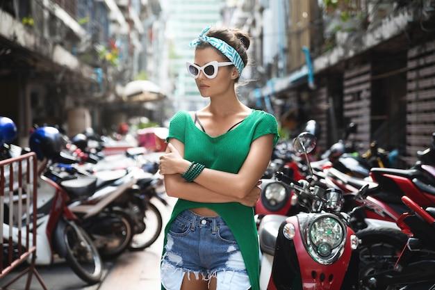 Stijlvol model met groen shirt en bandana poseert op de parkeerplaats met veel scooters