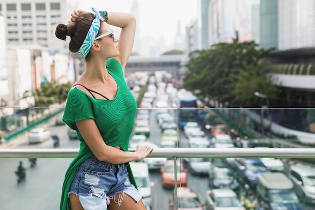 Stijlvol model met groen shirt en bandana poseren op de brug naast de snelweg
