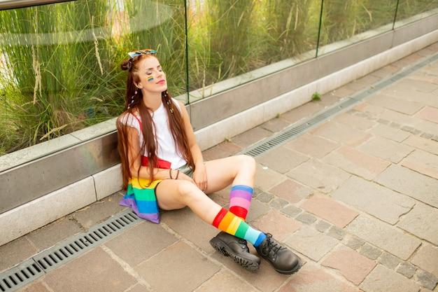 Stijlvol model met kleurrijke accessoires en lgbt-vlag op haar gezicht buitenshuis poseren.