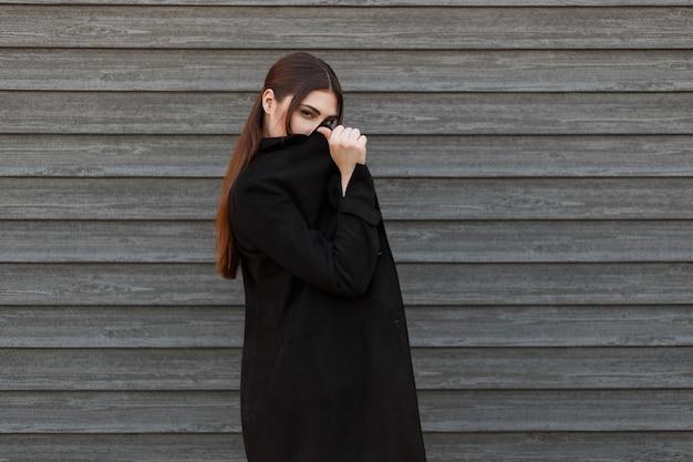 Stijlvol modelmeisje in een zwarte modevacht bedekt haar gezicht bij een houten muur
