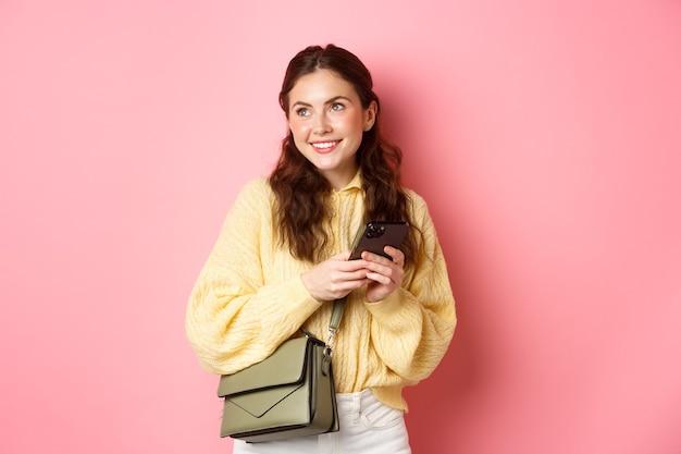 Stijlvol modern meisje met tevreden glimlach, romantisch opzij kijken, chatten op dating-app op smartphone, staande met tas tegen roze muur