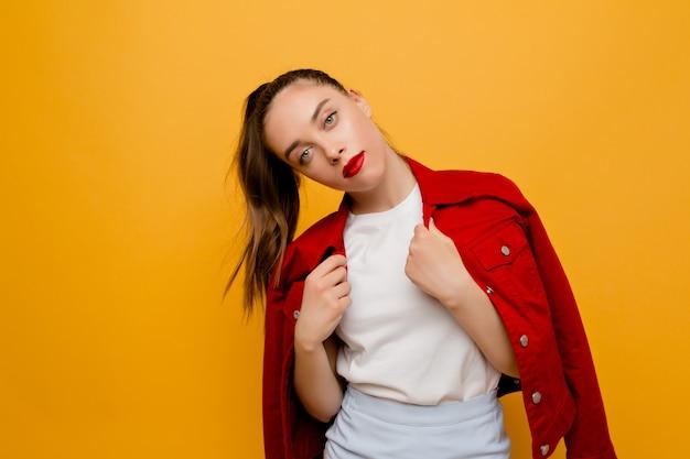 Stijlvol modern vrouwelijk model gekleed rood jasje, wit t-shirt en blauwe rok met rode lippenstift vormt op geïsoleerde muur. mode, stijl, look, model, plaats voor tekst
