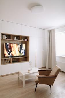 Stijlvol modern woonkamerinterieur met tv, fauteuil, salontafel en een raam met gordijnen.