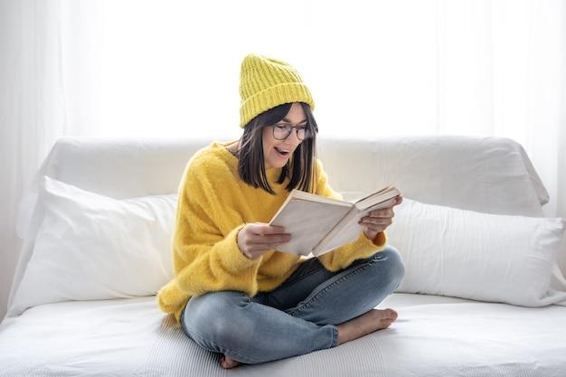Stijlvol mooi donkerbruin meisje in glazen en een hoed leest een boek op de bank. zelfontplooiing en hobby-concept.