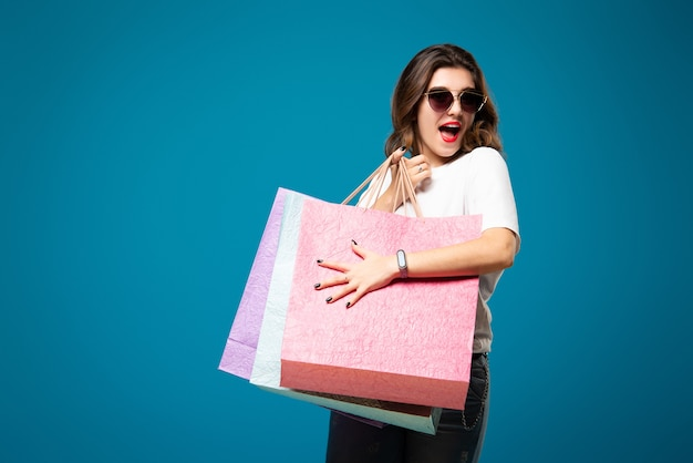 Stijlvol mooi meisje in zonnebril loopt met veelkleurige boodschappentassen