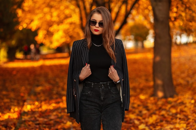 Stijlvol mooi meisje met vintage zonnebril in een modieus zwart elegant pak met een blazer wandelt in de natuur met kleurrijk herfstoranje blad