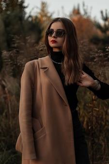 Stijlvol mooi meisje met vintage zonnebril in een modieuze jas met een trui in het gras op de natuur