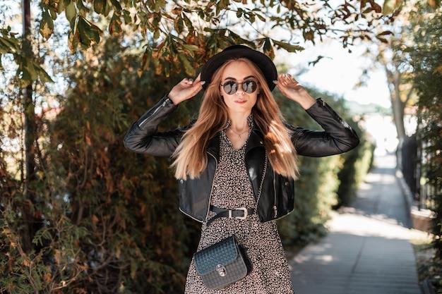 Stijlvol mooi meisje met zonnebril en een hoed in een modieuze jurk met een leren jas en een zwarte handtas loopt in de buurt van het herfstgebladerte in de stad