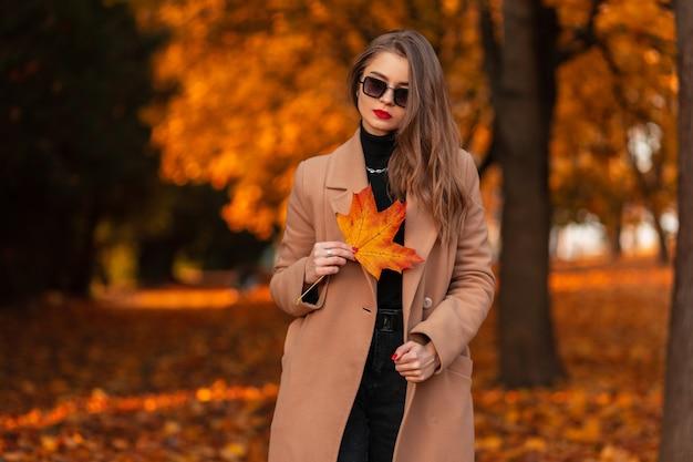 Stijlvol mooi meisje met zonnebril in modieuze kleding en een jas met een oranjerood blad loopt in een herfstpark met gouden bladeren