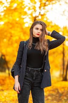 Stijlvol mooi zakenmeisje met rode lippen in een modeblazer en zwarte vintage trui loopt in een herfstpark met gekleurd geel herfstgebladerte bij zonsondergang