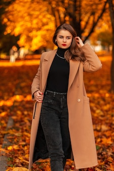 Stijlvol mooi zakenmeisje met rode lippen in een modieuze beige jas met een trui en zwarte spijkerbroek loopt in een park met gekleurd herfstgebladerte