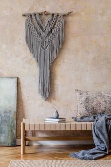 Stijlvol oosters woonkamerinterieur met beige chaise longue, grijs macramé, kussen, plaid, tapijt, boek en elegante persoonlijke accessoires. wabi sabi concept. grunge muur. ontwerp huisdecoratie. sjabloon
