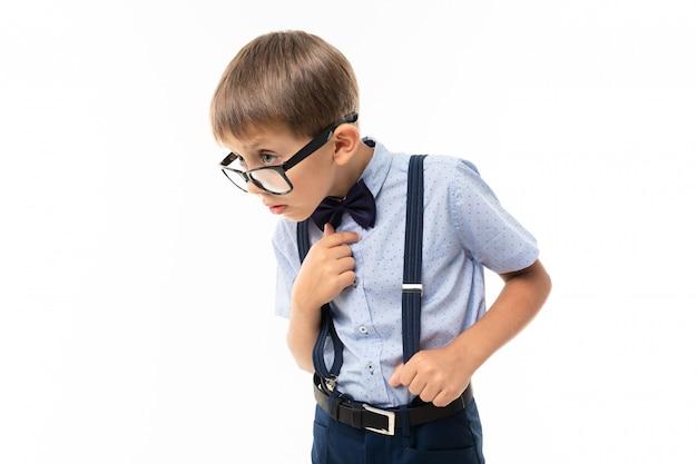 Stijlvol opgeleide jongen in glazen en een klassiek pak bewijst iets op een witte muur